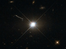 """This image from Hubble's Wide Field and Planetary Camera 2 (WFPC2) is likely the best of ancient and brilliant quasar 3C 273, which resides in a giant elliptical galaxy in the constellation of Virgo (The Virgin). Its light has taken some 2.5 billion years to reach us. Despite this great distance, it is still one of the closest quasars to our home. It was the first quasar ever to be identified, and was discovered in the early 1960s by astronomer Allan Sandage. The term quasar is an abbreviation of the phrase """"quasi-stellar radio source"""", as they appear to be star-like on the sky. In fact, quasars are the intensely powerful centres of distant, active galaxies, powered by a huge disc of particles surrounding a supermassive black hole. As material from this disc falls inwards, some quasars — including 3C 273 — have been observed to fire off super-fast jets into the surrounding space. In this picture, one of these jets appears as a cloudy streak, measuring some 200 000 light-years in length. Quasars are capable of emitting hundreds or even thousands of times the entire energy output of our galaxy, making them some of the most luminous and energetic objects in the entire Universe. Of these very bright objects, 3C 273 is the brightest in our skies. If it was located 30 light-years from our own planet — roughly seven times the distance between Earth and Proxima Centauri, the nearest star to us after the Sun — it would still appear as bright as the Sun in the sky.  WFPC2 was installed on Hubble during shuttle mission STS-61. It is the size of a small piano and was capable of seeing images in the visible, near-ultraviolet, and near-infrared parts of the spectrum."""